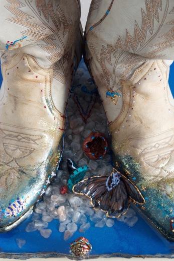 Souvenir d'enfance (détail), bottes de cowboy, résine, cendres de bois, branche, broderie, cerne relief, peinture, papillon, sel de l'Himalaya noyau de pêche, coquille de noix de Grenoble, 30 cm x 30 cm x 47 cm, 2018